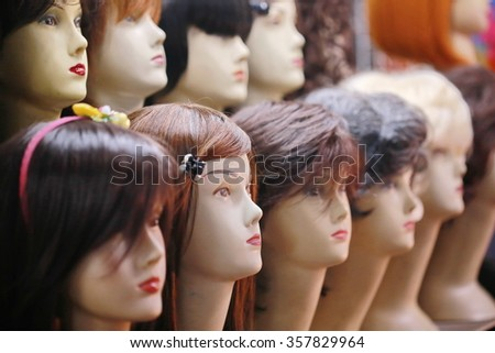 wigs on mannequin heads, a row of mannequins on a shelf in a wig shop - stock photo
