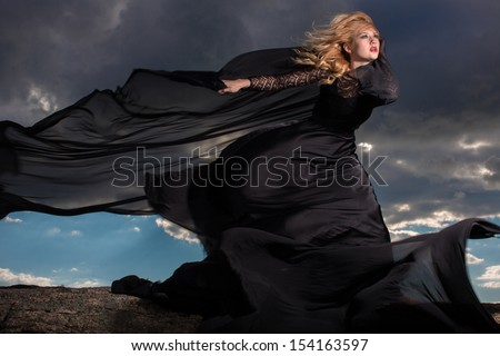 Wind blowing blond hair and long black dress of the young girl standing on the mount