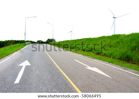 windmills in a green meadow and road way - stock photo