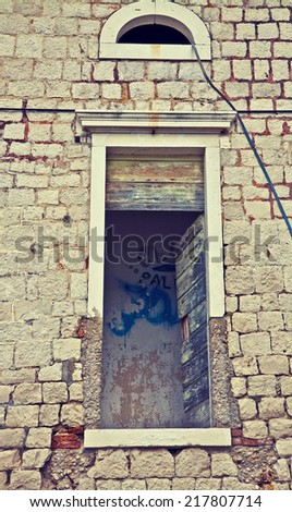 Window detail of a ruined and abandoned building with graffiti inside.  Instagram-like retro effect added. - stock photo