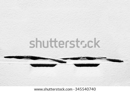 Windscreen wipers and a snow covered car - stock photo