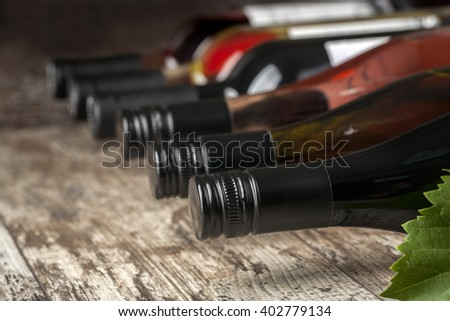 wine bottles stacked on wooden table shot with limited depth of field - stock photo