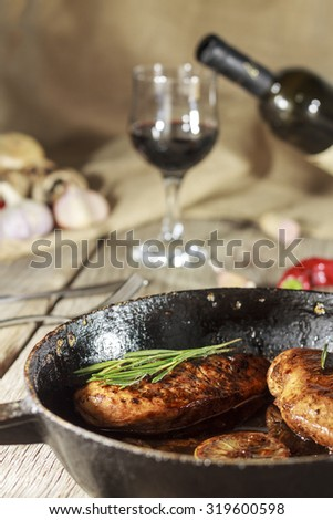Wine in a glass and a bottle of wine. Grilled meat. Frying pan. Vegetables on a wooden table. Rustic style.  - stock photo