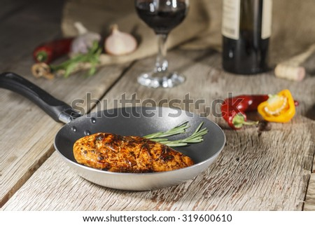 Wine in a glass and a bottle of wine.  Protein. Grilled meat. Frying pan. Vegetables on a wooden table. Rustic style.  - stock photo