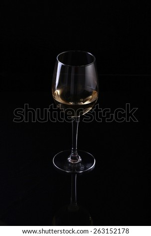 Wineglass with white wine standing on reflective black background - stock photo