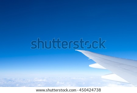 Wing of the plane on blue sky background, view from window of airplane.