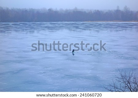 Winter fishing on the ice first. Misty winter morning                             - stock photo