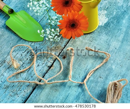 2017  with a rope,  flowers and gardening tools on blue wooden background