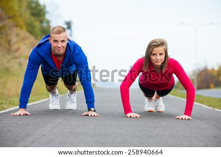 Woman and man doing push-ups - stock photo