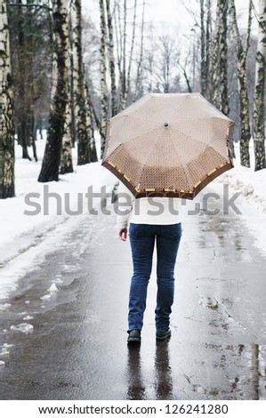 Woman at rainy and snowy day in early spring - stock photo