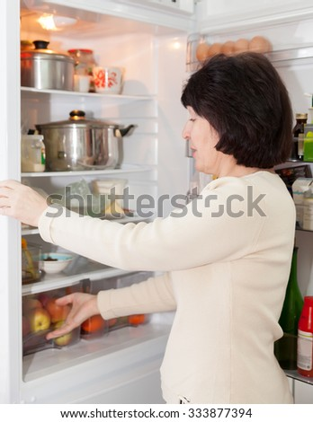 woman checking   food in   refrigerator at  kitchen. - stock photo