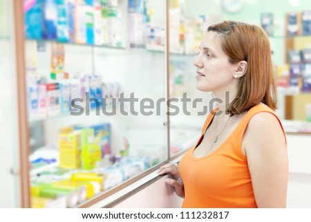 woman chooses drugs at the pharmacy drugstore