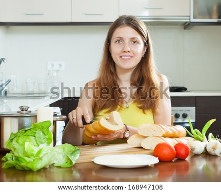 woman cooking sandwiches with  baguette
