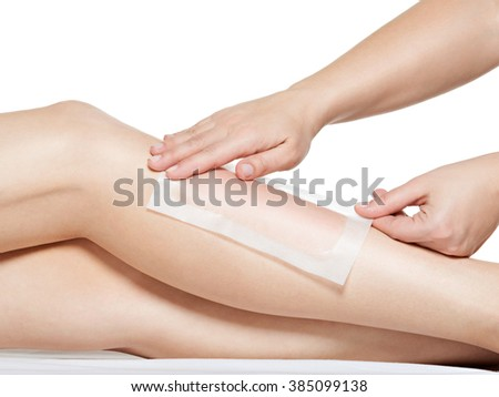 woman depilates her legs by waxing -  studio on white background