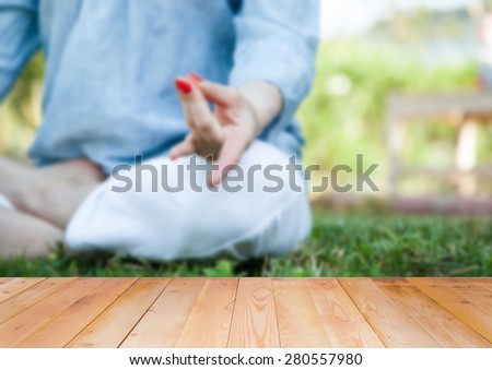 Woman doing yoga in the park, blurred background - stock photo