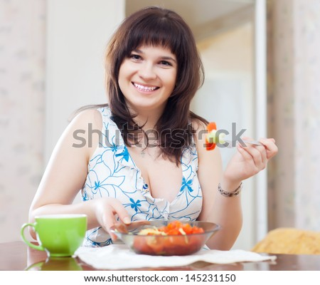 woman eats vegetables salad at home