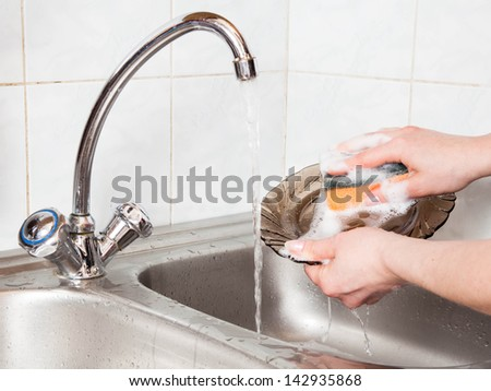 woman hands rinsing dishes under running water in the sink - stock photo
