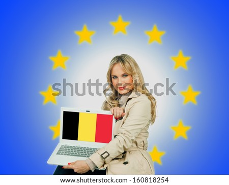 woman holding laptop with belgium flag on the screen and european union stars in the background - stock photo