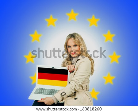 woman holding laptop with german flag on the screen and european union stars in the background - stock photo