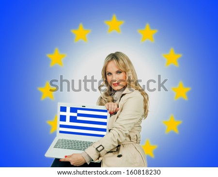woman holding laptop with greece flag on the screen and european union stars in the background - stock photo