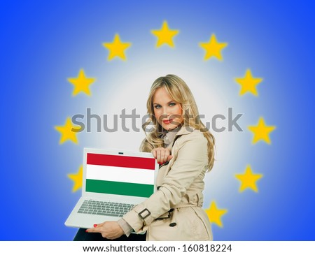 woman holding laptop with hungary flag on the screen and european union stars in the background - stock photo