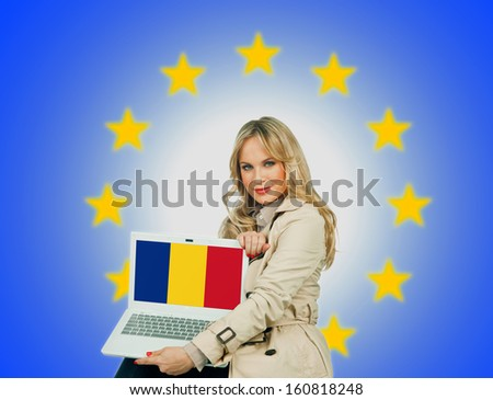 woman holding laptop with romanian flag on the screen and european union stars in the background - stock photo