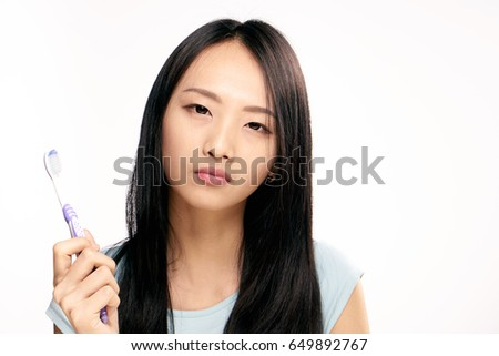 Woman holding toothbrush in hand on isolated background