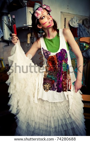 woman in artist studio with paint on face  holding paint brushes in hand looking for inspiration - stock photo