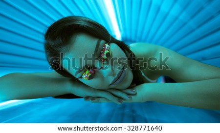Woman in bed solarium with protect glasses - stock photo