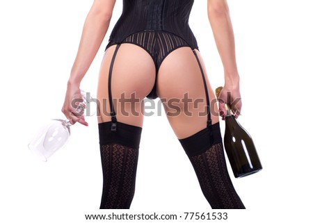 Woman in black stockings keeps a bottle of wine. Isolated on white background.