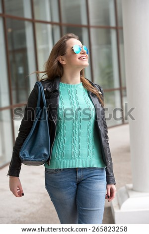 Woman in blue sweater and with blue sunglasses. Fashion girl.