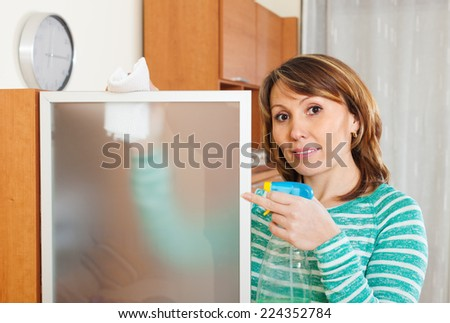 woman in green cleaning  glass with detergent at home