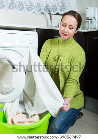 woman in green doing laundry with washing machine at home kitchen