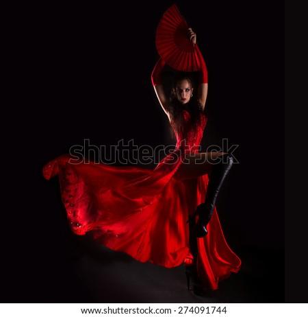 Woman in long red dress posing in studio - stock photo