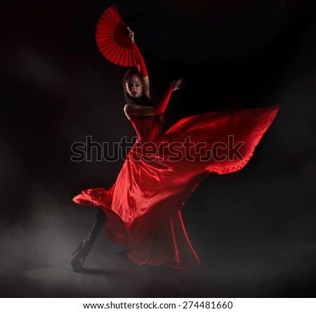 Woman in long red dress stay in dancing pose.