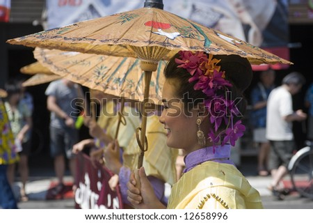 woman in traditional clothes with water dripping of her face during songkran festival in Chiang Mai, Thailand. - stock photo