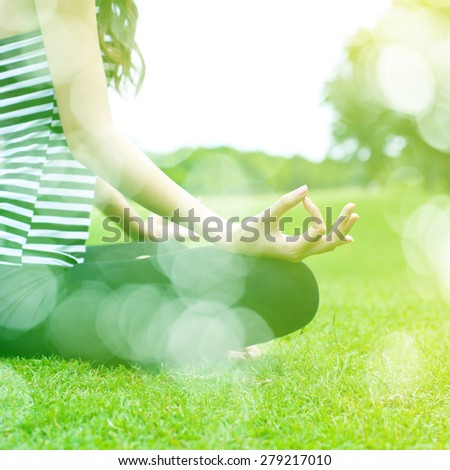 Woman meditating in a yoga pose on vintage color filter effect. - stock photo