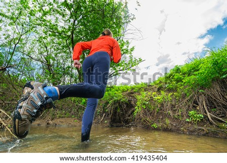 Woman running through a streambed.