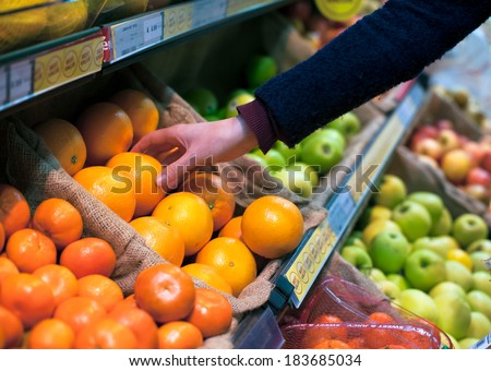 woman's hand choosing orange in grocery store - stock photo