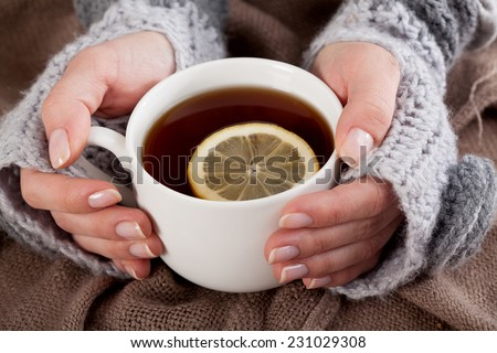Woman's hand holding cup of tea with lemon on a cold day - stock photo