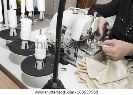 woman sews clothes on sewing machine - stock photo