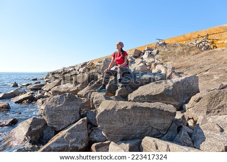 Woman sitting on a stone next to mountain bike relaxing and enjoying nature  - stock photo