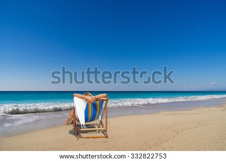 woman sitting on a sun louger  at the beach