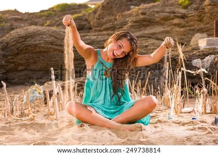 woman sitting on the beach sand - stock photo