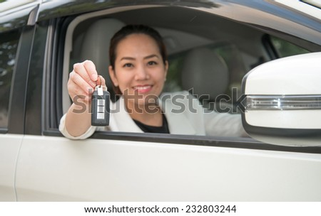 woman smiling showing new car keys and car - stock photo