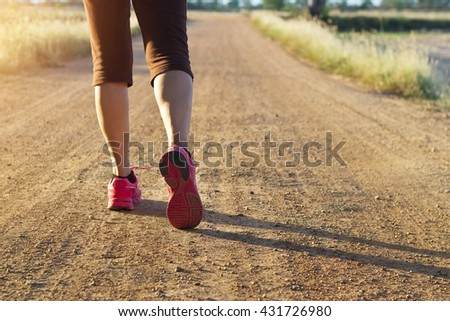 Woman walking exercise on trail in summer nature  - stock photo