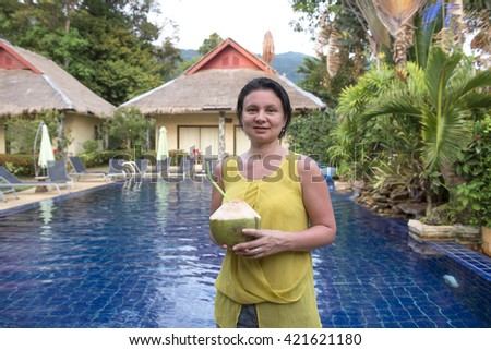 Woman with a coconut in her hands near the swimming pool - stock photo