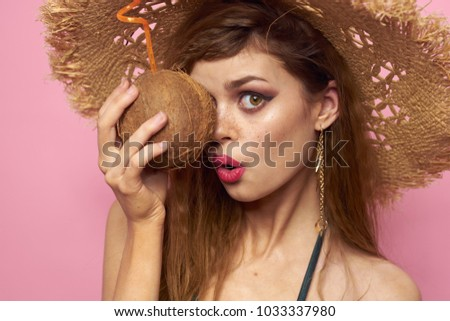 woman with a coconut on a pink background, sunburn, rest, summer, exotic