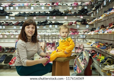 woman with child chooses baby shoes at fashionable shop