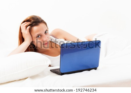woman with laptop on white sheet in her bed at home